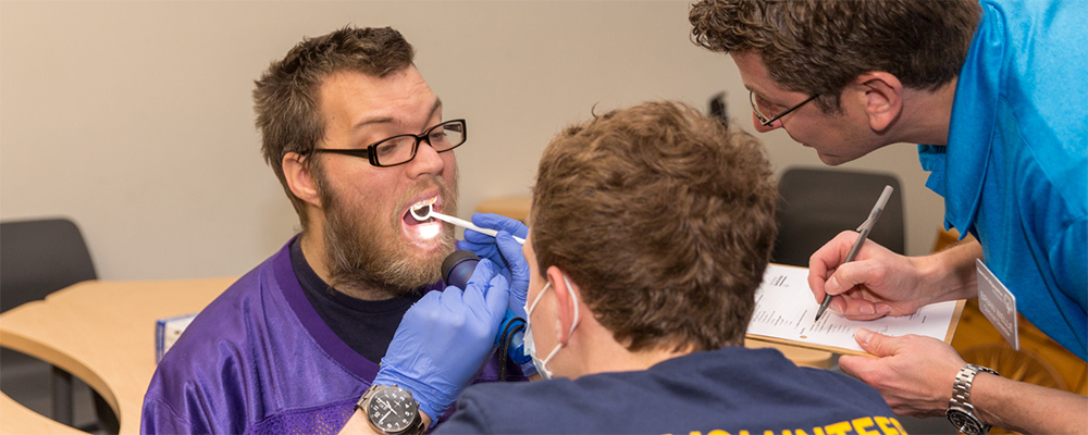 Two dental volunteers inspect a Special Olympics Minnesota athlete's mouth