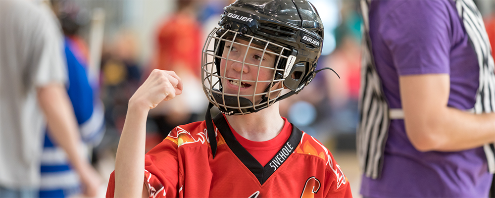 A Special Olympics Minnesota athlete wearing a poly hockey goalie mask looks to the left and raises a hand