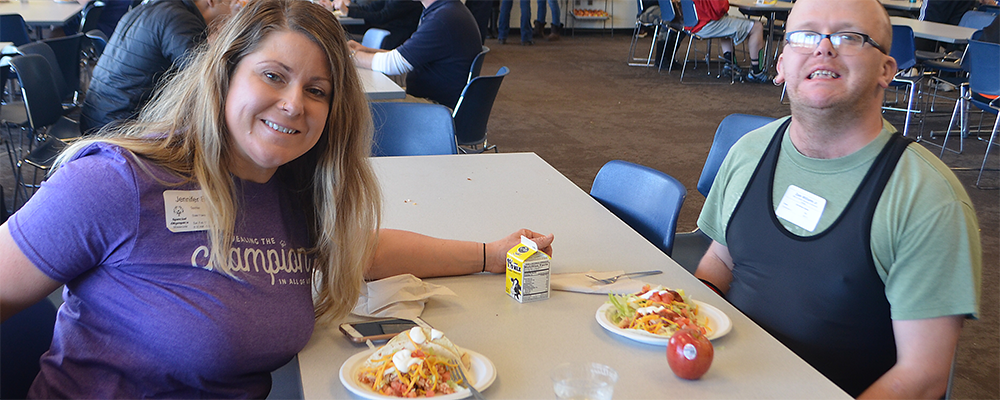 A Special Olympics Minnesota volunteer eats lunch with an athlete
