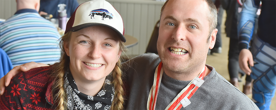 A Special Olympics Minnesota athlete wearing a gold medal and his friend smile
