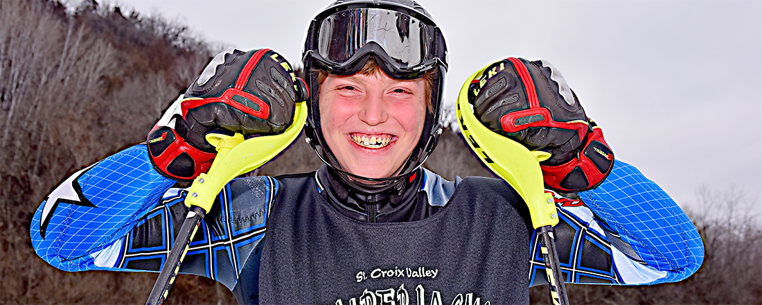A Special Olympics Minnesota skier holds up his ski poles and smiles