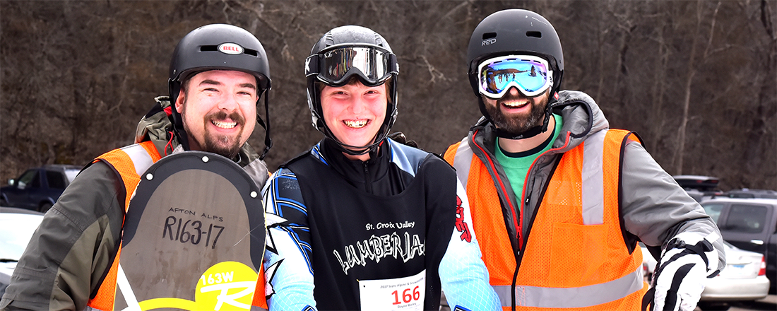 Three skiers/snowboarders smile at the camera