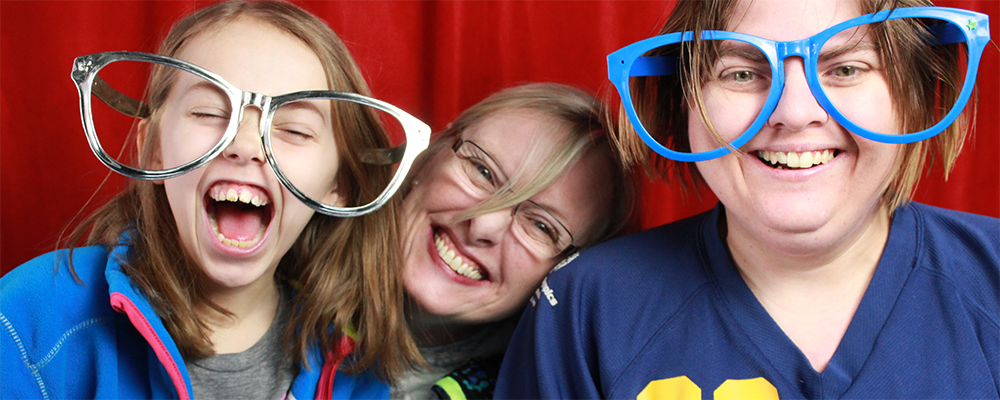 Two Special Olympics Minnesota athletes in comically-oversized glasses laugh while a woman between them smiles at the camera
